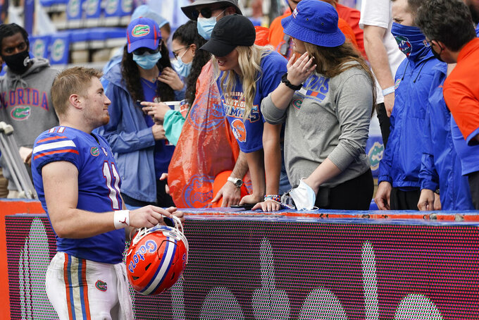 Florida quarterback Kyle Trask (11) greets friends in the stadium after defeating Kentucky during in an NCAA college football game, Saturday, Nov. 28, 2020, in Gainesville, Fla. (AP Photo/John Raoux)