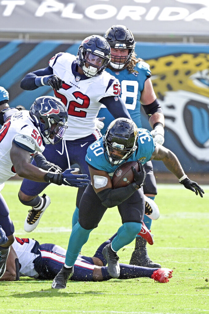 Jacksonville Jaguars running back James Robinson (30) runs for yardage against Houston Texans linebacker Tyrell Adams (50) and linebacker Jonathan Greenard (52) during the first half of an NFL football game, Sunday, Nov. 8, 2020, in Jacksonville, Fla. (AP Photo/Phelan M. Ebenhack)