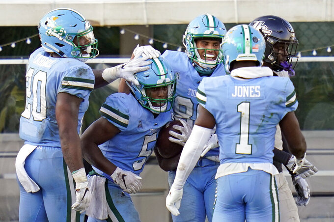 Tulane running back Stephon Huderson (5) celebrates his 9-yard touchdown run against Central Florida with running back Cameron Carroll (20), wide receiver Mykel Jones (1) and wide receiver Sorrell Brown, second from right, during the second half of an NCAA college football game Saturday, Oct. 24, 2020, in Orlando, Fla. (AP Photo/John Raoux)