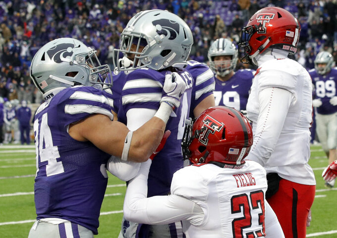 Kansas State wide receiver JaQuay Lane (4) is congratulated by Kansas State running back Alex Barnes (34) after scoring a touchdown while covered by Texas Tech defensive back Damarcus Fields (23) during the first half of an NCAA college football game in Manhattan, Kan., Saturday, Nov. 17, 2018. (AP Photo/Orlin Wagner)