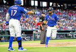 Texas Rangers' Rougned Odor, right, is congratulated by Shin-Soo Choo (17) after scoring on an RBI single by Jeff Mathis during the third inning of a baseball game against the Houston Astros Thursday, July 11, 2019, in Arlington, Texas. (AP Photo/Jeffrey McWhorter)