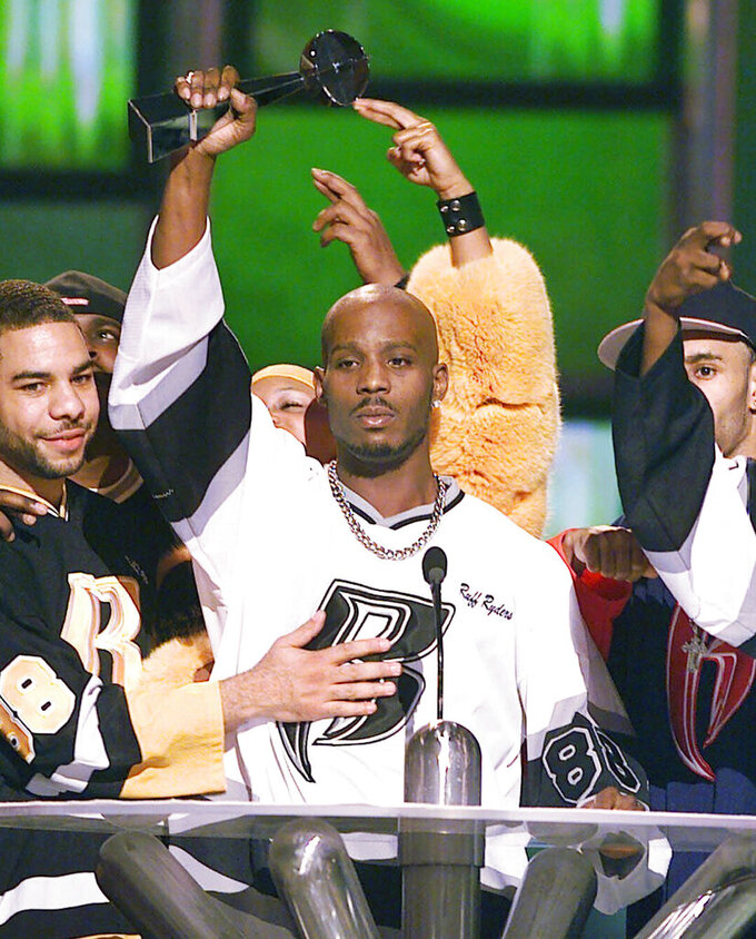 """FILE - DMX, center, accepts the R&B Album Artist of the Year during the 1999 Billboard Music Awards in Las Vegas, on Dec. 8, 1999. The family of rapper DMX says he has died at age 50 after a career in which he delivered iconic hip-hop songs such as """"Ruff Ryders' Anthem."""" A statement from the family says the Grammy-nominated rapper died at a hospital in White Plains, New York, """"with his family by his side after being placed on life support for the past few days. He was rushed to a New York hospital from his home April 2. (AP Photo/Laura Rauch, File)"""