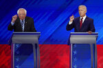 In this Sept. 12, 2019, photo, Sen. Bernie Sanders, I-Vt., left, and former Vice President Joe Biden, right, talk during a Democratic presidential primary debate hosted by ABC at Texas Southern University in Houston. (AP Photo/David J. Phillip)