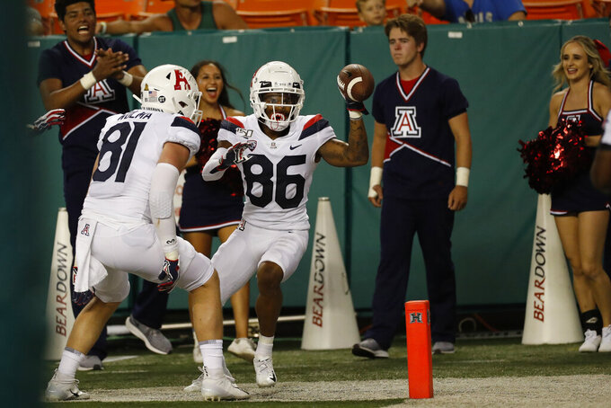 After scoring a second half touchdown against Hawaii, Arizona wide receiver Stanley Berryhill III (86) and Arizona tight end Bryce Wolma (81)during an NCAA college football game, Saturday, Aug. 24, 2019, in Honolulu. (AP Photo/Marco Garcia)