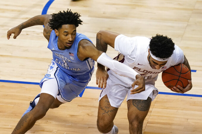 North Carolina guard Leaky Black (1) scrambles for the ball along with Florida State guard Anthony Polite (2) during the first second of an NCAA college basketball game in the semifinal round of the Atlantic Coast Conference tournament in Greensboro, N.C., Friday, March 12, 2021. (AP Photo/Gerry Broome)