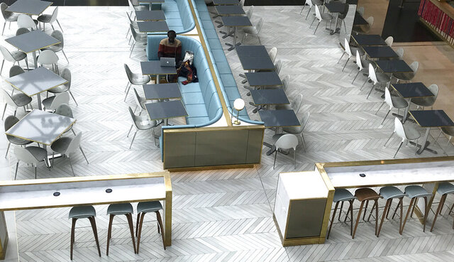 A man sits alone at a coffee shop area at a shopping centre in London, Tuesday, March 17, 2020. For most people, the new coronavirus causes only mild or moderate symptoms, such as fever and cough. For some, especially older adults and people with existing health problems, it can cause more severe illness, including pneumonia. (AP Photo/Kirsty Wigglesworth)