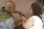 In this Aug. 21, 2021, image taken from video, firearms instructor Wayne Thomas shows Valerie Rupert the proper hand position on a fire arm at the Recoil Firearms store in Taylor, Mich. Rupert was among 1,000 or so mostly Black women taking part in free weekend gun safety and shooting lessons at two Detroit-area ranges. Black women like Rupert increasingly are considering gun ownership for personal protection, according to industry experts and gun rights advocates. (AP Photo/Carlos Osorio)