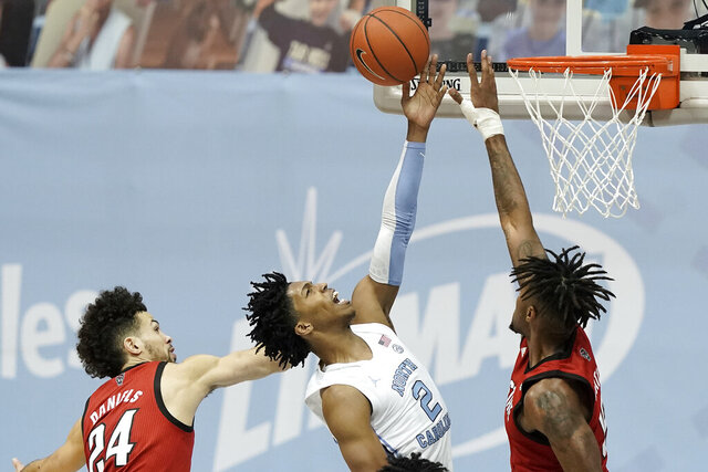 North Carolina guard Caleb Love (2) drives to the basket against North Carolina State guard Devon Daniels (24) and forward Manny Bates during the second half of an NCAA college basketball game in Chapel Hill, N.C., Saturday, Jan. 23, 2021. (AP Photo/Gerry Broome)