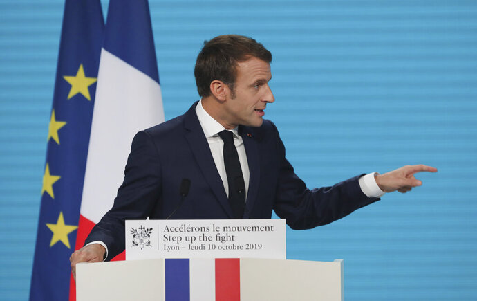 France's President Emmanuel Macron gestures as he delivers a speech at the Lyon's congress hall, central France, Thursday, Oct. 10, 2019, during the meeting of international lawmakers, health leaders and people affected by HIV, Tuberculosis and malaria. Lyon is hosting the two day Global Fund event aimed at raising money to help in the global fight against the epidemics. (AP Photo/Laurent Cipriani)
