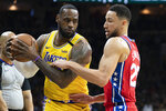 Los Angeles Lakers' LeBron James, left, tries to make his move on Philadelphia 76ers' Ben Simmons, right, during the first half of an NBA basketball game, Saturday, Jan. 25, 2020, in Philadelphia. (AP Photo/Chris Szagola)