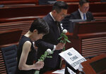 Pro-democracy lawmakers pay a silent tribute to the man who fell to his death on Saturday evening after hanging a protest banner on scaffolding on a shopping mall, at the Legislative Council in Hong Kong, Wednesday, June 19, 2019.  Hong Kong lawmakers are meeting for the first time in a week, after massive protests over an extradition bill that eventually was suspended.(AP Photo/Vincent Yu)