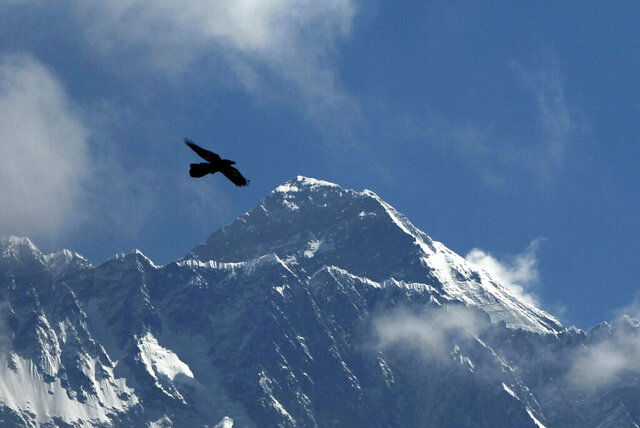 FILE - In this May 27, 2019, file photo, a bird flies with Mount Everest seen in the background from Namche Bajar, Solukhumbu district, Nepal. China and Nepal have jointly announced on Tuesday, Dec. 8, 2020, a new height for Mount Everest, ending a discrepancy between the two nations. The new official height is 8,848.86 meters (29,032 feet), slightly more than Nepal's previous measurement and about four meters higher than China's. (AP Photo/Niranjan Shrestha, File)