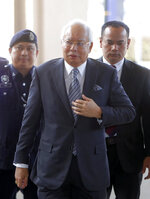 Malaysian former Prime Minister Najib Razak, center, walks in High Court of Malaya in Kuala Lumpur, Malaysia, Friday, Aug. 10, 2018. Najib was charged of money laundering on Wednesday over a multibillion-dollar graft scandal at a state investment fund, the Malaysia anti-corruption agency said. (AP Photo/Yam G-Jun)