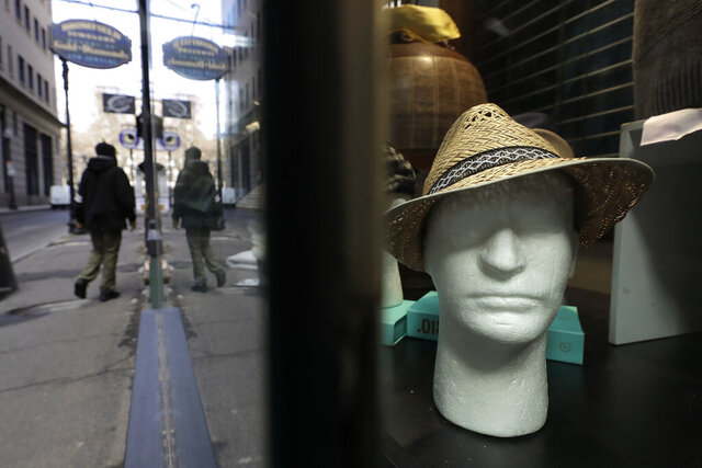 A hat rests on a mannequin in a store window, Tuesday, March 24, 2020, in Boston. Mass. Gov. Charlie Baker ordered all nonessential businesses to close by Tuesday afternoon March 24, and remain closed until at least April 7 in an effort to slow down the spread of the new coronavirus.(AP Photo/Steven Senne)