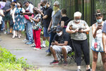 Steven Posey checks his phone as he waits in line to vote, Tuesday, June 9, 2020, at Central Park in Atlanta. Voters reported wait times of three hours. (AP Photo/John Bazemore)