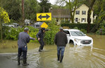 A group of men walk by a stranded car in flood water outside the Farmhouse Inn Wednesday, Feb. 27, 2019, in Forestville, Calif.   The National Weather Service says the Russian River in Sonoma County topped 32 feet Tuesday evening and it could crest at more than 46 feet by Wednesday night. (AP Photo/Eric Risberg)