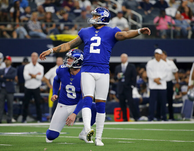 New York Giants kicker Aldrick Rosas (2) and Daniel Jones (8) watch the flight of the successful field goal in the second half of a NFL football game against the Dallas Cowboys in Arlington, Texas, Sunday, Sept. 8, 2019. (AP Photo/Michael Ainsworth)