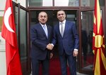 Turkey's Foreign Minister Mevlut Cavusoglu, left, shakes hands with North Macedonia's Foreign Minister Nikola Dimitrov, right, prior to their meeting, in Skopje, North Macedonia, Tuesday, July 16, 2019. Cavusoglu on Tuesday downplayed as