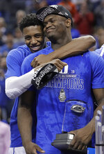 Duke's RJ Barrett, left, hugs Zion Williamson after Duke defeated Florida State in the NCAA college basketball championship game of the Atlantic Coast Conference tournament in Charlotte, N.C., Saturday, March 16, 2019. (AP Photo/Nell Redmond)