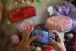 Ada Mendoza, 24, takes a picture of the decorations at her baby shower as her nuclear family, her partner, and close friends celebrate at her parents' home in the Catia neighborhood of Caracas, Venezuela, Saturday, Sept. 5, 2020. Her partner's family, who live just outside the capital, didn't attend the shower due to the travel restrictions brought by the COVID-19 pandemic lockdown, and lack of gasoline, amid a nation-wide fuel crunch. (AP Photo/Matias Delacroix)