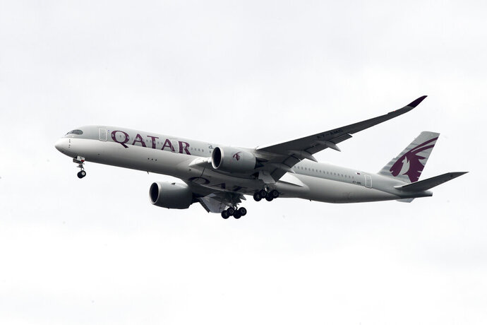 FILE - In this Nov. 7, 2019 file photo, a Qatar Airways jet approaches Philadelphia International Airport in Philadelphia. Long-haul carrier Qatar Airways said Wednesday, May 6, 2020, it will fire staff as the coronavirus pandemic largely has grounded the global aviation industry. (AP Photo/Matt Rourke, File)