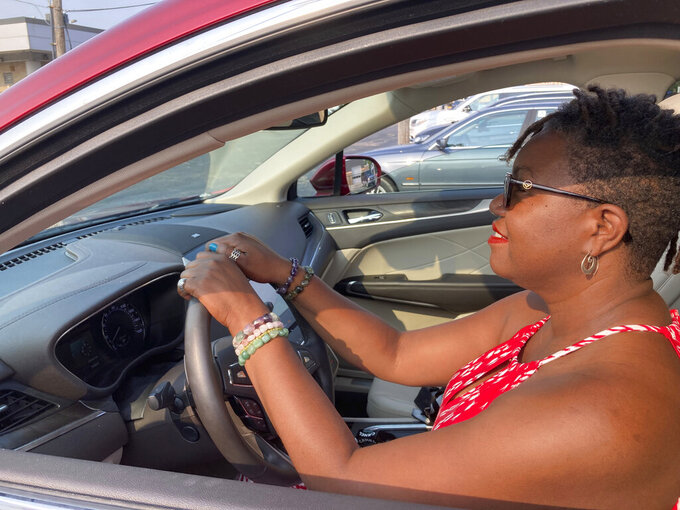 Jessica Pitts sits behind the wheel of a 2019 Lincoln MKC on the lot of Jack Demmer Lincoln in Dearborn, Mich., on Monday, July 19, 2021. Pitts bought the used car at the dealership. A seemingly endless streak of skyrocketing used vehicle prices is finally coming to a close in the U.S., according to the latest data (AP Photo/Mike Householder)
