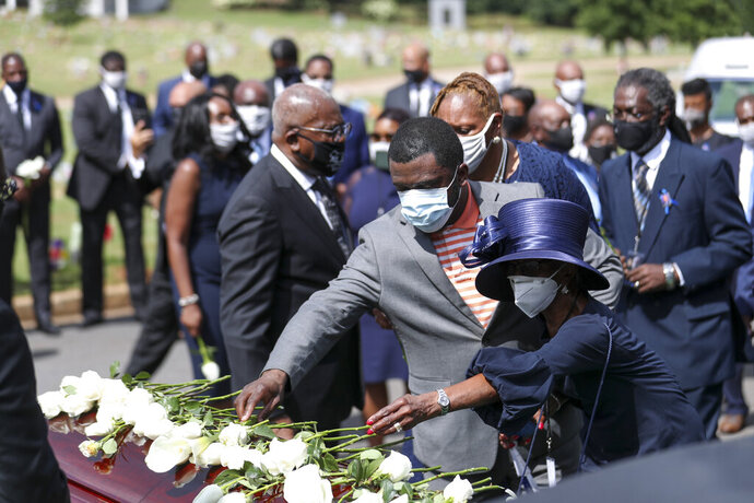 Family members place flowers on the casket of Rep. John Lewis during the burial service at South-View Cemetery in Atlanta Thursday, July 30, 2020. (Alyssa Pointer/Atlanta Journal-Constitution via AP, Pool)