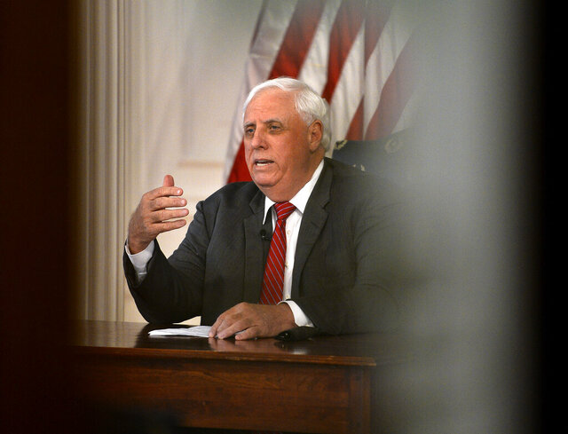 In this March, 23, 2020 file photo West Virginia Gov. Jim Justice issues a stay at home order, effective 8 p.m. Tuesday from his office in the WV State Capitol in Charleston, W.Va. Justice has expanded his aggressive plan to lift coronavirus restrictions after announcing new hotspots in the state's eastern panhandle. The Republican governor on Thursday, May 21, 2020 said he is considering a mandatory face mask order for Berkeley and Jefferson counties after at least 35 new cases were reported there in a single day. He has dispatched the National Guard to the region to assess the situation.  (Kenny Kemp/Charleston Gazette-Mail via AP, file)