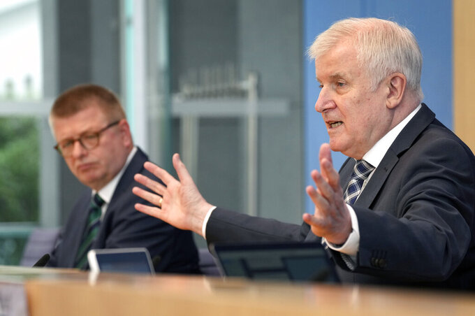 German Interior Minister Horst Seehofer, right, and Thomas Haldenwang, left, head of the German Federal Office for the Protection of the Constitution, address the media during a press conference on the 'Constitution Protection Report 2020' in Berlin, Germany, Tuesday, June 15, 2021. (AP Photo/Michael Sohn, pool)