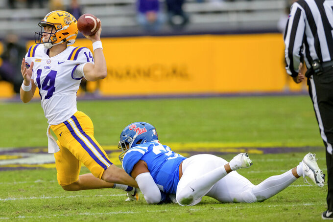 LSU quarterback Max Johnson (14) throws to avoid a sack by Mississippi linebacker Jacquez Jones (32) during the first half of an NCAA college football game in Baton Rouge, La., Saturday, Dec. 19, 2020. (AP Photo/Matthew Hinton)