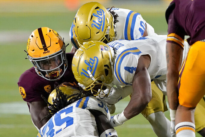 Arizona State running back Rachaad White, left, is hit by UCLA linebacker Carl Jones (35), defensive back Stephan Blaylock (4) and linebacker Caleb Johnson (40) during the first half of an NCAA college football game Saturday, Dec. 5, 2020, in Tempe, Ariz. (AP Photo/Matt York)
