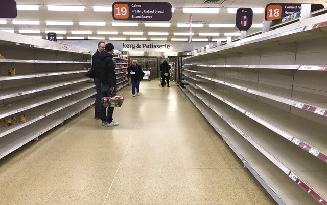FILE - In this Thursday, March 19, 2020 file photo, people stand in an aisle of empty shelves in a supermarket in London,  amid panic-buying due to the coronavirus outbreak. A pandemic forcing everyone to stay home could be the perfect moment for online grocery services. In practice, they've been struggling to keep up with a surge in orders, highlighting their limited ability to respond to an unprecedented onslaught of demand. After panic buying left store shelves stripped of staples like pasta, canned goods and toilet paper, many shoppers quickly found online grocery delivery slots almost impossible to come by, too. (AP Photo/Kirsty Wigglesworth, File)