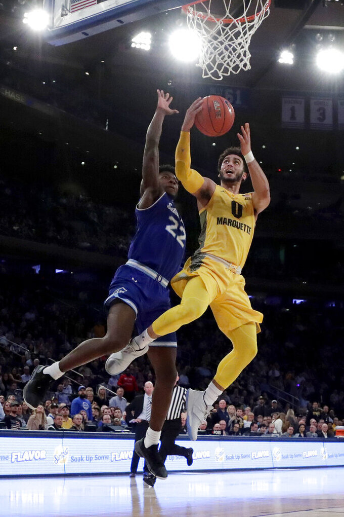 Marquette guard Markus Howard (0) goes up for a shot against Seton Hall guard Myles Cale (22) during the first half of an NCAA college basketball semifinal game in the Big East men's tournament, Friday, March 15, 2019, in New York. (AP Photo/Julio Cortez)