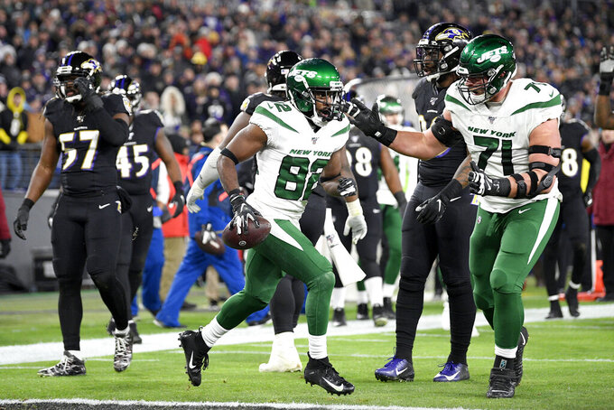 New York Jets wide receiver Jamison Crowder (82) celebrates his touchdown catch with offensive guard Alex Lewis (71) during the first half of an NFL football game against the Baltimore Ravens, Thursday, Dec. 12, 2019, in Baltimore. (AP Photo/Nick Wass)