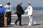 """FILE - In this July 22, 2017, file photo, President Donald Trump shakes hands with Ship Captain Rick McCormack as he arrives for the the commissioning ceremony of the aircraft carrier USS Gerald R. Ford (CVN 78) at Naval Station Norfolk, Va. Trump's vision of America's tomorrows looks much like its yesterdays. He loves """"beautiful"""" coal. """"Beautiful"""" warships. And """"those four beautiful words: MADE IN THE USA!"""" He speaks of the country's might as measured by its steel mills, farms and cars rolling off Detroit assembly lines. (AP Photo/Carolyn Kaster, File)"""