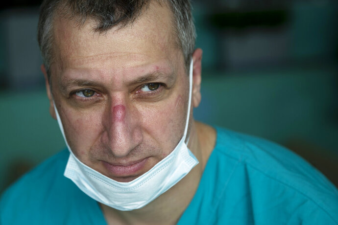 In this photo taken on Friday, May 15, 2020, Dr. Osman Osmanov has a rest after his shift at an intensive care unit of the Filatov City Clinical Hospital in Moscow, Russia. Moscow accounts for about half of all of Russia's coronavirus cases, a deluge that strains the city's hospitals and has forced Osmanov to to work every day for the past two months, sometimes for 24 hours in a row. (AP Photo/Pavel Golovkin)