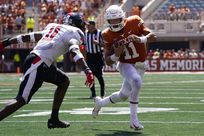 Texas quarterback Casey Thompson, right, scrambles as Texas Tech defensive back Eric Monroe, left, defends during the second half of an NCAA college football game on Saturday, Sept. 25, 2021, in Austin, Texas. (AP Photo/Chuck Burton)