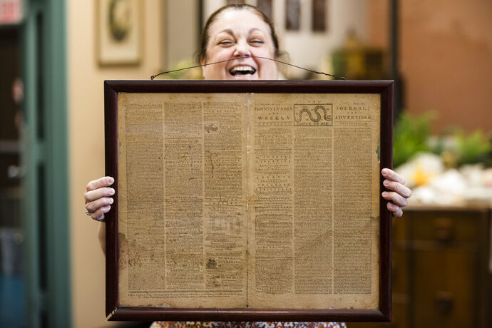 FILE - In this Thursday, Oct. 25, 2018 file photo, Heather Randall displays a Dec. 28, 1774 Pennsylvania Journal and the Weekly Advertiser at the Goodwill Industries South Jersey in Bellmawr, N.J.  An original 1774 Philadelphia newspaper that was discovered at a New Jersey Goodwill is heading to a Philadelphia philosophy society founded by Benjamin Franklin. (AP Photo/Matt Rourke)