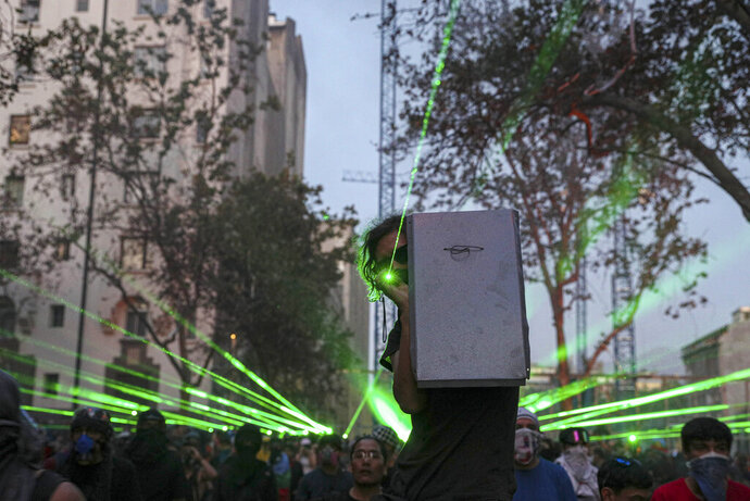 In this Thursday, Nov. 14, 2019 photo, anti-government demonstrators shine laser pointers a the police during a protest in Santiago, Chile. Students in Chile began protesting nearly a month ago over a subway fare hike. The demonstrations have morphed into a massive protest movement demanding improvements in basic services and benefits, including pensions, health, and education. (AP Photo/Esteban Felix)