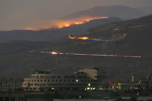 FILE - In this Saturday, Oct. 31, 2020 file photo, forest burns in the mountains after shelling by Azerbaijan's artillery during a military conflict outside Stepanakert, the separatist region of Nagorno-Karabakh. Armenia accused neighboring Azerbaijan of systematically promoting ethnic hatred against Armenia citizens, as the two nations that fought a six-week war last year faced off at a United Nations court on Thursday Oct. 14, 2021. (AP Photo/File)