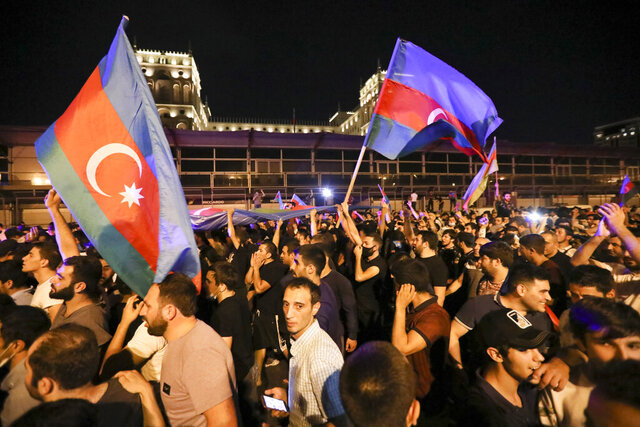 People carry Azerbaijn's national flags as they rally in support of Azerbeijan's Army in Baku, Azerbaijan, Tuesday, July 14, 2020. Skirmishes on the volatile Armenia-Azerbaijan border escalated Tuesday, marking the most serious outbreak of hostilities between the neighbors since the fighting in 2016. (AP Photo/Aziz Karimov)