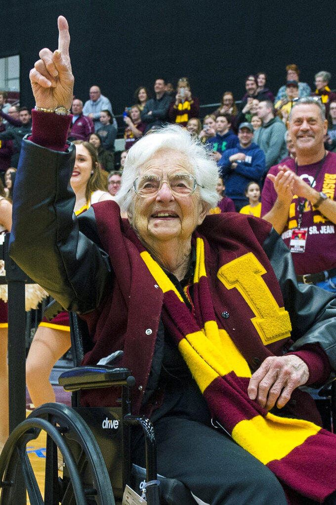 FILE - In this March 25, 2018, file photo, Sister Jean Dolores-Schmidt, chaplain of the Loyola-Chicago basketball team, gestures during a rally for the team in Chicago. One of the lasting memories of the 2018 tournament was the Ramblers' telegenic now-100-year-old team chaplain, Sister Jean Dolores-Schmidt. What they did on the court was pretty memorable, too. (Tyler LaRiviere/Chicago Sun-Times via AP, File)