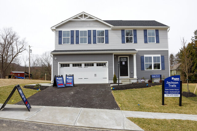 FILE - On March 18, 2020, model homes and for sale signs line the streets as construction continues at a housing plan in Zelienople, Pa.   U.S. home prices grew more slowly in May 2020, but continued to show resilience in the face of the coronavirus outbreak. (AP Photo/Keith Srakocic, File)