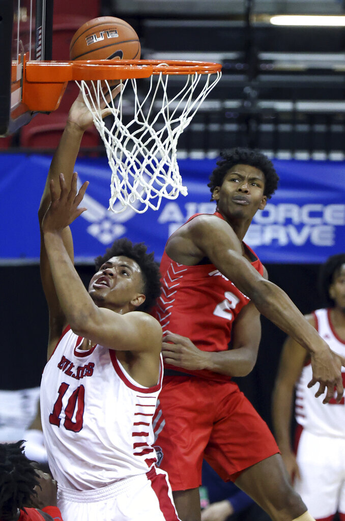 Fresno State forward Orlando Robinson (10) shoots as New Mexico guard Saquan Singleton (2) defends during the second half of an NCAA college basketball game in the first round of the Mountain West Conference men's tournament Wednesday, March 10, 2021, in Las Vegas. (AP Photo/Isaac Brekken)