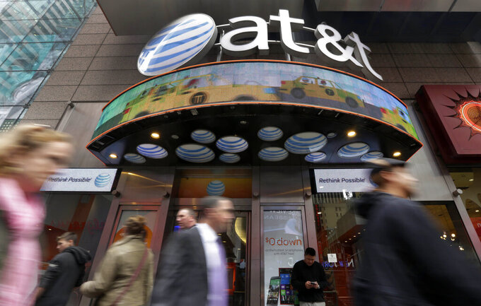 FILE - In this Oct. 21, 2014 file photo, people pass an AT&T store in New York's Times Square. AT&T will combine its media operations that include CNN HBO, TNT and TBS in a $43 billion deal with Discovery, the owner of lifestyle networks including the Food Network and HGTV.  The deal announced Monday, May 17, 2021, would create a separate media company as households increasingly abandon cable and satellite TV, looking instead at Netflix, Amazon Prime Video, Facebook, TikTok and YouTube. (AP Photo/Richard Drew, File)