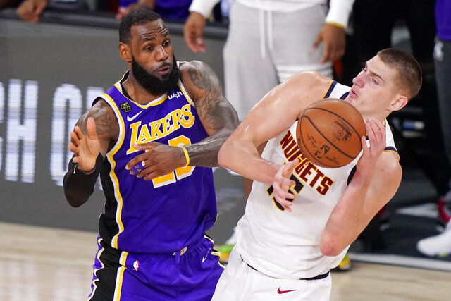 Los Angeles Lakers' LeBron James (23) and Denver Nuggets' Nikola Jokic (15) battle for the ball during the second half of an NBA conference final playoff basketball game Saturday, Sept. 26, 2020, in Lake Buena Vista, Fla. The Lakers won 117-107 to win the series 4-1. (AP Photo/Mark J. Terrill)
