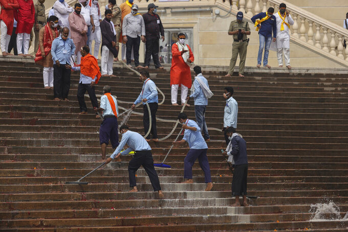 Workers clean the steps as thousands of devotees arrive to take holy dips in the Ganges River during Kumbh Mela, or pitcher festival, one of the most sacred pilgrimages in Hinduism, in Haridwar, northern state of Uttarakhand, India, Monday, April 12, 2021. Tens of thousands of Hindu devotees gathered by the Ganges River for special prayers Monday, many of them flouting social distancing practices as the coronavirus spreads in India with record speed. (AP Photo/Karma Sonam)