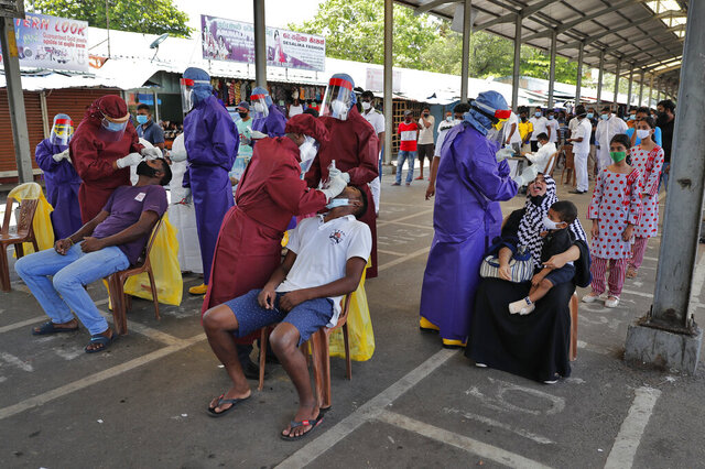 Sri Lankan health workers take a swab samples to test for COVID-19 in Colombo, Sri Lanka, Thursday, Oct. 22, 2020. (AP Photo/Eranga Jayawardena)