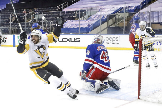 Pittsburgh Penguins' Pierre-Olivier Joseph celebrates the game winning goal by Sidney Crosby against New York Rangers' Alexandar Georgiev (40) in an NHL hockey game Saturday, Jan. 30, 2021, in New York. (Bruce Bennett/Pool Photo via AP)