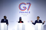 FILE - In this Sunday Aug. 25, 2019 file photo French President Emmanuel Macron, right, African Development Bank President Akinwumi Adesina, left, and UNICEF ambassador Angelique Kidjo attend a press conference on the situation in Sahel during the G7 summit in Biarritz, southwestern France. One of Africa's iconic artists, Kiddo, is the voice of a new project aimed at rewriting laws across the African continent that keep millions of women from becoming a more powerful economic force. (Ian Langsdon Pool via AP, File)